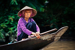 A woman is being transported by boat in the Mekong Delta.