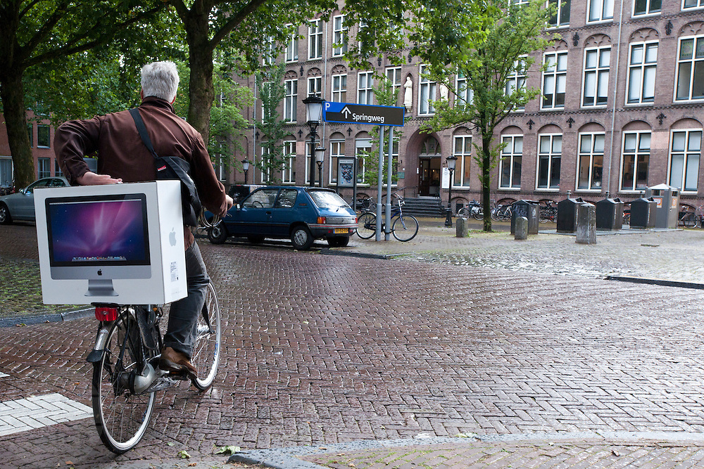Een man fietst met een net aangeschafte Apple iMac.<br /> <br /> A man is bringing his new iMac home by bike