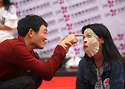 JINAN, CHINA - APRIL 29: (CHINA OUT)<br /> <br /> Staring Contest With Facial Masks <br /> <br />  An organizer tantalizes a participant during Staring Contest at Luoyuan Street on April 29, 2105 in Jinan, Shandong province of China. A Staring Contest held by a plastic surgery hospital attracted nearly 50 boys and girls that participants should wear facial masks and could not move or even other facial expressions.<br /> ©Exclusivepix Media