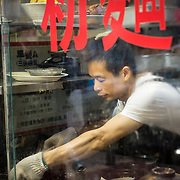 Man preparing food behind a steamed window in Kowloon, Hong Kong