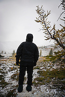 A person all dressed in black winter clothes looking out on a alpine landscape, Enchantment Lakes Wilderness Area, Washington Cascades, USA.