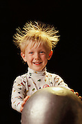 Static electricity. Young boy holding the dome of a Van de Graaff generator, which makes his hair stand on end. The generator creates a negative charge of static electricity. When the boy touches the dome the charge passes from the dome (where it would otherwise be stored) on to his hands, and through to his hair. As the individual hairs become charged they repel each other, causing them to stand on end. Photographed at the Franklin Institute, Philadelphia, USA. MODEL RELEASED (1991)