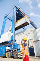 Worker using walkie-talkie in shipping yard