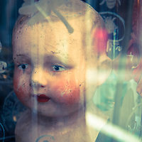 An old cracked dolls head in a jar in the window of an antique shop.