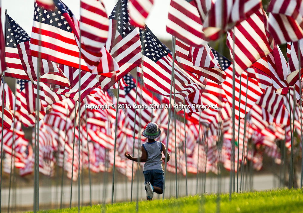 A girl runs through amongst 3,000 US flags are displayed at Pepperdine University to mark the 14th anniversary of the 9/11 terror attack, September 10, 2015 in Malibu, California.  Photo by Ringo Chiu/PHOTOFORMULA.com)