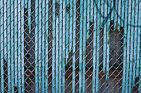 Chain link fence with wooden broken slats.