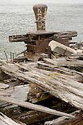 old rotting wooden pier with an big industrial rusty bollard
