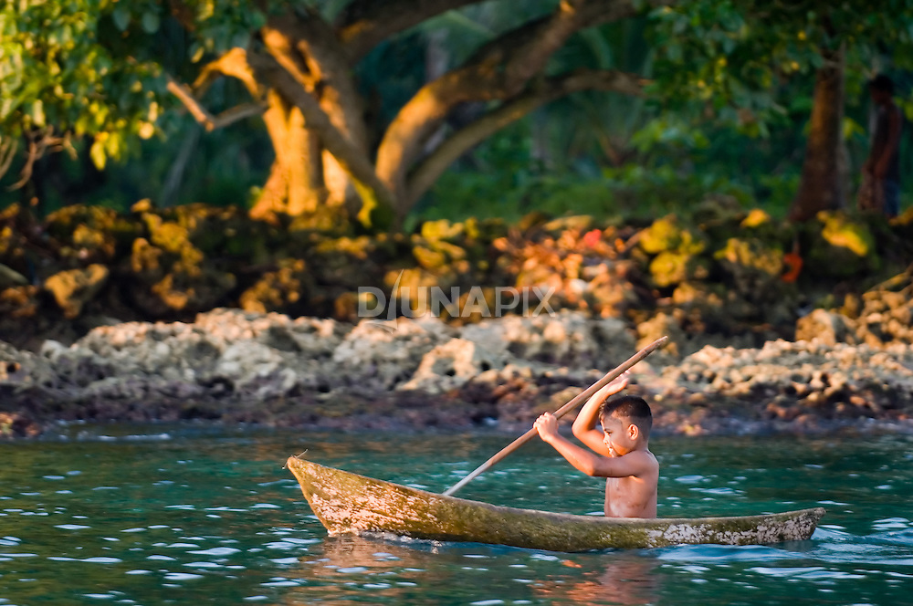 A boy paddles a small dugout canoe in front of Waghena village.