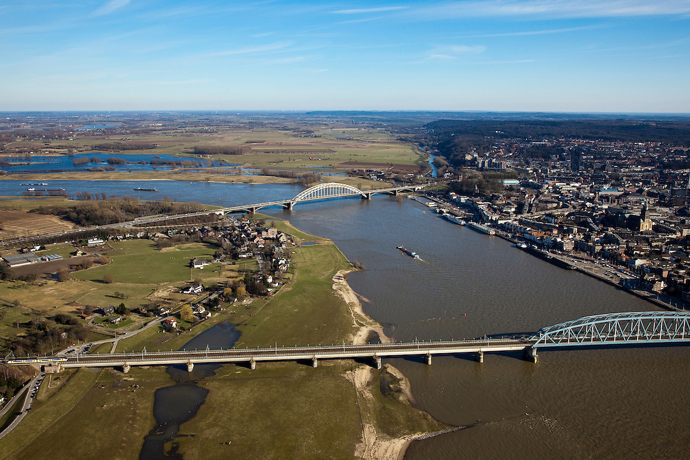 Nederland, Gelderland, Nijmegen, 07-03-2010; Waal met Waalbrug, rechts de binnenstad, links het dorp Lent. Waalsprong: aan de noordoever van de Waal, rond het dorp Lent zal een nieuw stadsdeel gebouwd gaan worden; ook wordt op deze lokatie een geul uitgegraven, meer landinwaarts ten opzicht van de rivier, om de rivier meer de ruimte te geven, Lent (aan de dijk) komt dan op een eiland te liggen..River Waal with Waal bridge, right inner city, left the village of Lent. Waalsprong (jump): on the north bank of the river, around the village of Lent, a new district will be build. And a flood trench will be dug (more inland) to give the river more space. Lent (at the dike) will be located on an island..luchtfoto (toeslag), aerial photo (additional fee required).foto/photo Siebe Swart