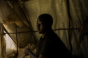 "KYANGWALI REFUGEE CAMP, UGANDA - MARCH 23: Mapenzi Dzanina, 16, at her family's tent in Kyangwali refugee resettlement camp in Uganda on March 23, 2018. ""We had heard that the Balendu were coming with their pangas, so we hid in the bush near our village. I was with some of my friends from school. We could see it as they burned the village but they couldn't see us. We were in the bush for two days, and then we spent another day in the boat, so I didn't eat for three days."" Violence in Ituri Province in northeastern Democratic Republic of Congo has displaced more than 100,000 people including approximately 40,000 refugees who have fled to Uganda. (Photo by Andrew Renneisen for The Washington Post)"