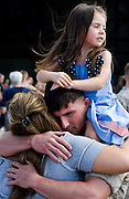 Marine24, nws, lynn, 1.-Sgt. Billy Harris hugs his former wife Natalie Jones ith his daughter Bailey Harris, 4, on his shoulders during the homecoming of Fox Company, the Milwaukee-based Marine Reserve unit with about 170 Marines and sailors returning to Wisconsin and their families.  Photo by Tom Lynn/TLYNN@JOURNALSENTINEL.COM