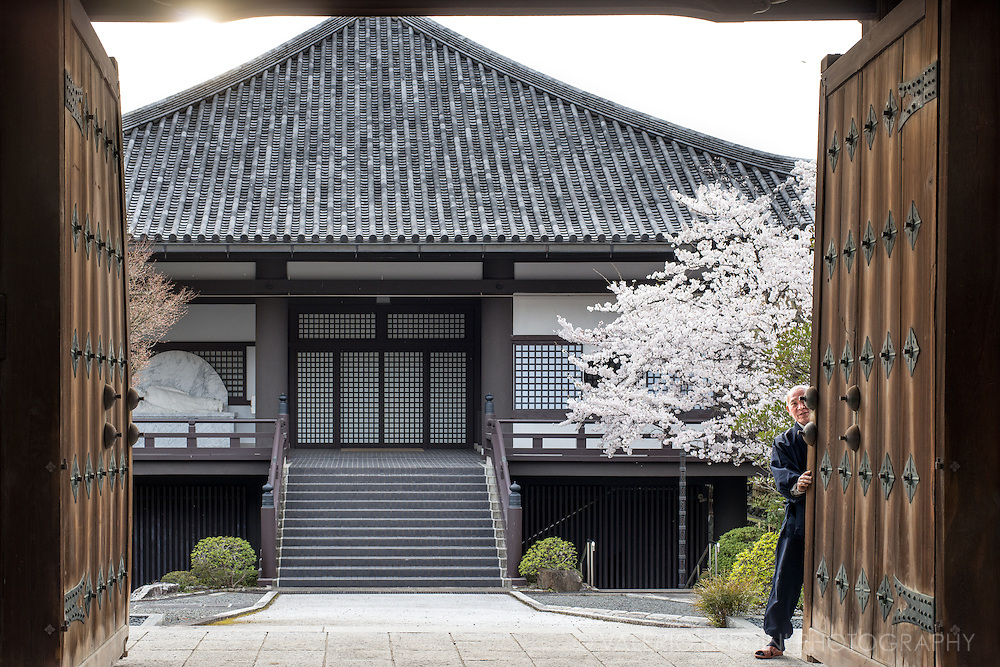 A man about to closing the gate of a traditional Japanese building in Kyoto.