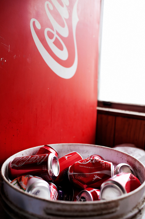 A trash can full of Coca-Cola cans sits next to a drink machine at Daneco Alligator Farm in Houma, Louisiana on Friday, February 19, 2010.
