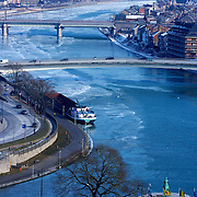 Sheets of ice cover part of the Meuse river running thru the heart of Namur, as if freezing the wave action of the still water.