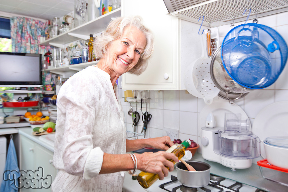 Portrait of senior woman pouring olive oil to saucepan in domestic kitchen