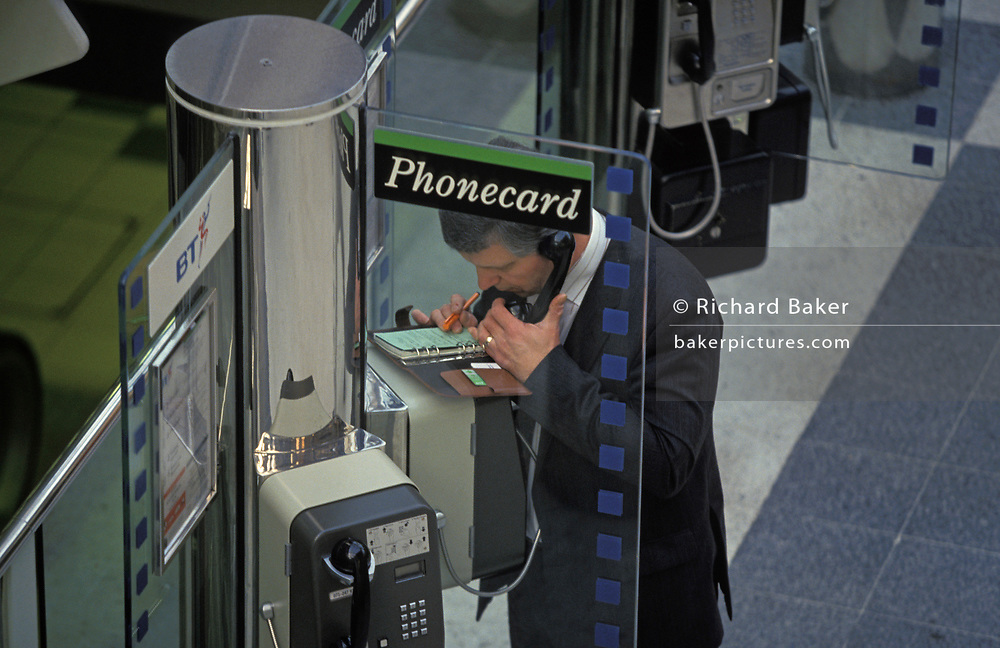 A businessman uses a BT public phone and makes notes with a ring-bound Filofax organiser, a pre-digital diary and appointments system used by professionals, on 16th June 1993, in Liverpool Street Station, London, England.