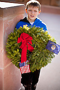 09 DECEMBER 2011 - PHOENIX, AZ:  A boy holds a Christmas wreath during a wreath laying ceremony in Phoenix. Several hundred volunteers and veterans gathered at the National Memorial Cemetery of Arizona in Phoenix Saturday to lay Christmas wreaths on headstones, a tradition started by Wreaths Across America. Wreaths Across America is a nonprofit organization founded to continue and expand the annual wreath laying ceremony at Arlington National Cemetery begun by Maine businessman, Morrill Worcester, in 1992.   PHOTO BY JACK KURTZ