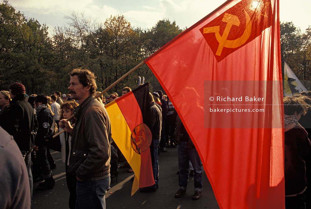 A year after the fall of the Berlin Wall and the end of the Communist Eastern Bloc era, pro-Communist Germans carrying Soviet and DDR flags march in Berlin, on 4th November 1990, in Berlin, Germany.