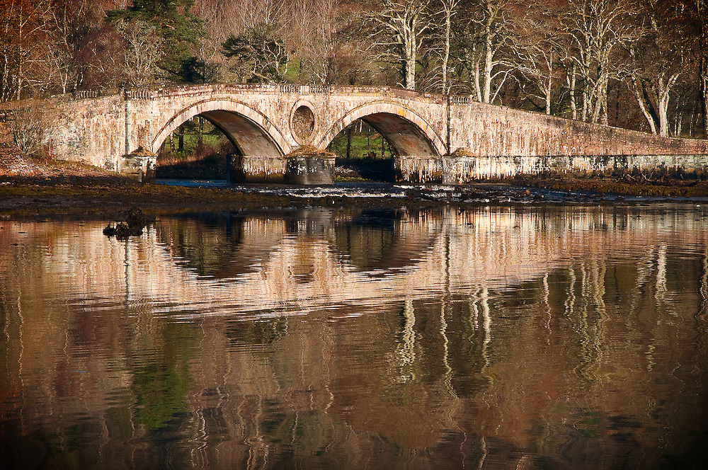 Ancient Inverary Bridge reflected in water