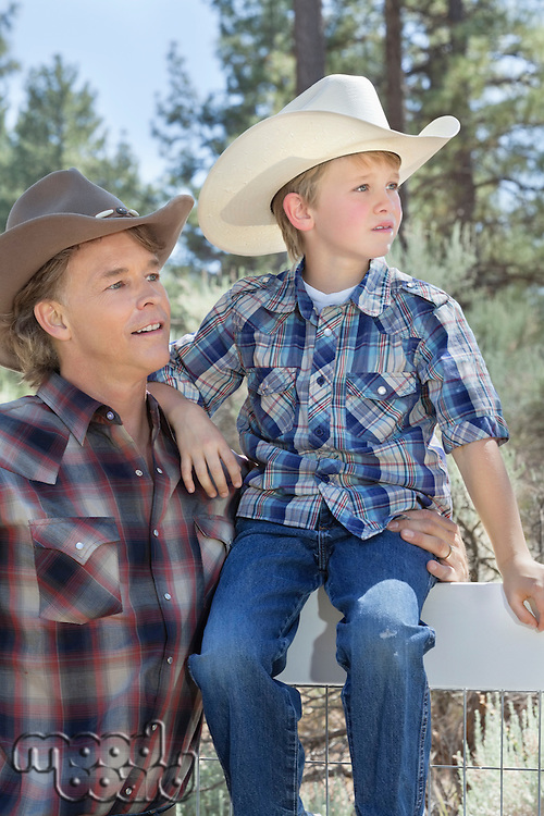 Mature father and son wearing cowboy hats looking away in park
