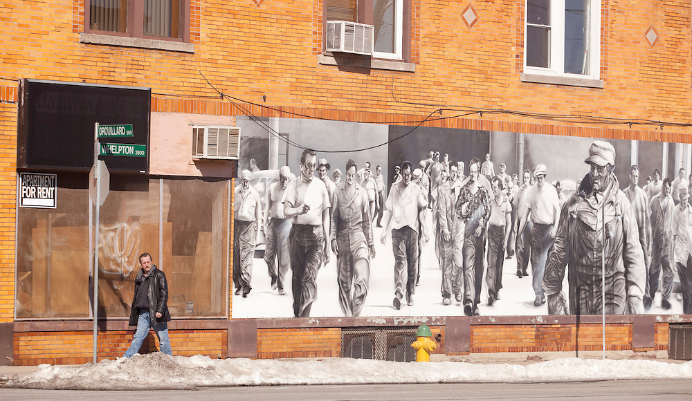 Windsor, Ontario ---10-02-19--- A man walks past a mural celebrating Windsor's manufacturing history in what is now a depressed area of town February 19, 2010.<br /> GEOFF ROBINS The Globe and Mail