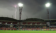Lightning strikes in the background during the 2014 AFL round 01 match between the GWS Giants and the Sydney Swans at Giants Stadium, Sydney on March 15, 2014. (Photo: Craig Golding/AFL Media)