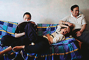 Khorloo Batsuuri uses her brother Batbileg's leg as a cushion on the sofa as she studies in the room they share with their parents Regzen Batsuuri (at right) and Oyuntsetseg Lhakamsuren (not in image). From coverage of revisit to Material World Project family in Ulaanbaatar, Mongolia, 2001.