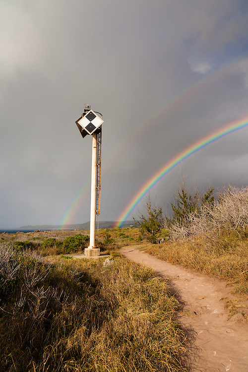 A clear double rainbow emerges form a summer storm over Kapalua along the coastal trail through dry shrublands. A nautical beacon stands sentinel next to this rocky coastline.