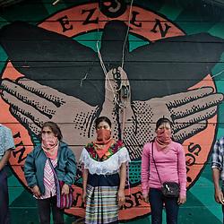A group of zapatists is posing in front of &quot;gran om&quot; murales.<br /> Un grupo de zapatistas posando adelante de un murales de &quot;gran om&quot;.