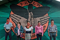 A group of zapatists is posing in front of &quot;gran om&quot; murales.<br />