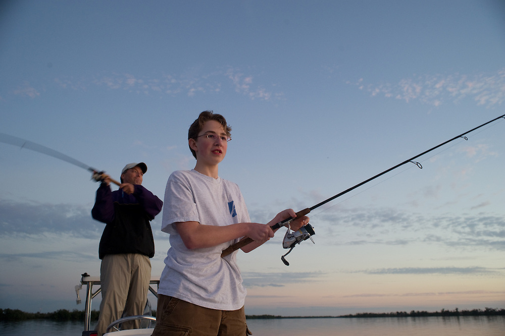 Man and Teenager fishing at sunset , gulf coast, Pine island  Florida