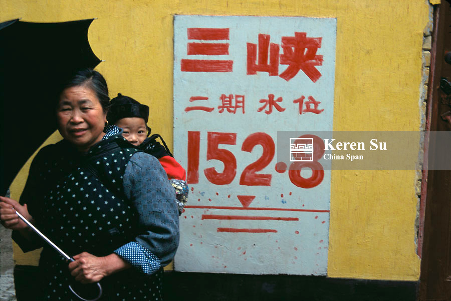 Woman carrying baby, sign of water level of the Three Gorges Dam Project on the wall, China,