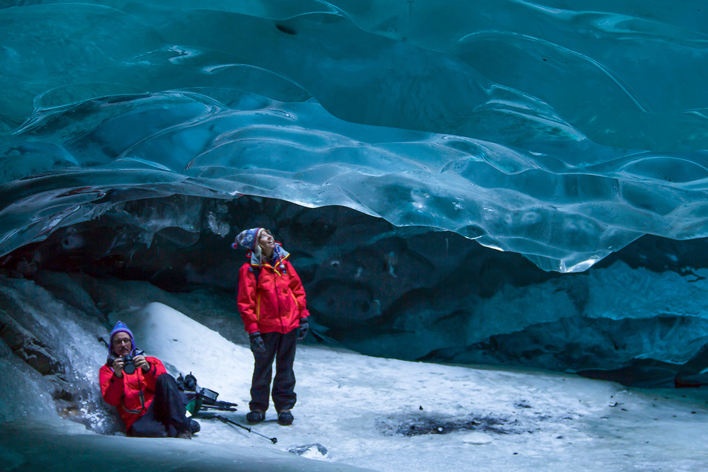 Photographers explore the intense blue ice cave beneath the Mendenhall Glacier.