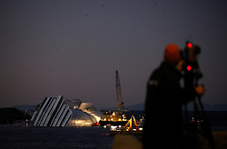 A TV cameraman films the Costa Concordia cruise ship which ran aground off the west coast of Italy at Giglio island January 25, 2012. The captain of the doomed Italian liner Costa Concordia said he was told by managers to take his ship close in to shore on the night it ran aground and capsized, according to bugged conversations leaked in Italian newspapers. <br /> REUTERS/Darrin Zammit Lupi (ITALY)