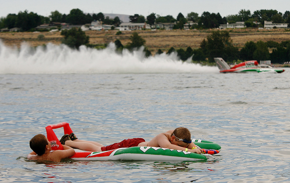 Theodore Morrison, 9, hangs on while Andrew Walli, 10, lays on an inflatable version of the U-6 Oh Boy! Oberto during Unlimited Heat #1C as Steve David speeds by in the real hydroplane.