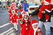 Israel, Haifa, Wadi Nisnas, Children dressed up as Santa Claus in a parade during the Holiday of holidays festival, celebrating Hanuka-Christmas-Ramadan December 2006