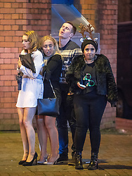 """© Licensed to London News Pictures . 16/12/2017. Manchester, UK. Four people huddle together for warmth as they wait at Deansgate Locks . Revellers out in Manchester City Centre overnight during """" Mad Friday """" , named for historically being one of the busiest nights of the year for the emergency services in the UK . Photo credit: Joel Goodman/LNP"""