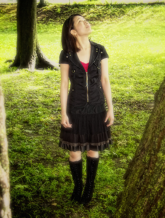 Young woman looks up towards the sky, surrounded my trees.