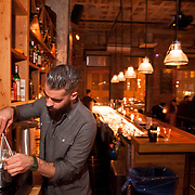"""November 18, 2013 - New York, NY : Bartender Maks Pazuniak works with a whisk and double boiler to make his winter-warming cocktail, the """"Bitter Coffee,"""" at The Counting Room on Berry Street in Williamsburg in Brooklyn on Monday evening.  The drink is comprised of Cynar, dark rum, maple syrup, an egg yolk, vanilla, coffee, and a grating of nutmeg.  CREDIT: Karsten Moran for The New York Times"""