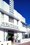 On a sunny day, a  young woman and little boy walk into the Art Deco, Streamline Moderne-style Century Hotel on Ocean Drive in South Beach. The building was designed by Henry Hohauser in 1939.