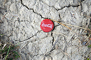 Coca Cola bottle with cap stuck in dried up sand