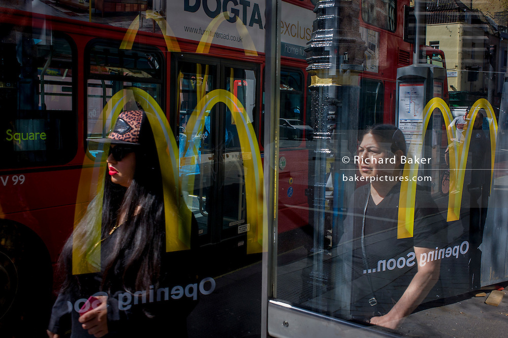 Multiple McDonalds arch logos seen through a central London bus shelter.