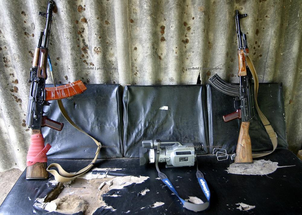 Georgien/Abchasien, Suchumi, 2006-08-28, Eine Kamera eines Journalisten zwischen zwei Kalaschnikows im zwischen Abchasen und Georgiern umkämpften Kodorital . Abchasien erklärte sich 1992 unabhängig von Georgien. Nach einem einjährigen blutigen Krieg zwischen den Abchasen und Georgiern besteht seit 1994 ein brüchiger Waffenstillstand, der von einer UNO-Beobachtermission unter personeller Beteiligung Deutschlands überwacht wird. Trotzdem gibt es, vor allem im Kodorital immer wieder bewaffnete Auseinandersetzungen zwischen den Armeen der Länder sowie irregulären Kämpfern. (A videocamera of a journalist between two kalashnikovs in the Kodori gorge, where abkhazian and georgian soldiers fighting each other. Abkhazia declared itself independent from Georgia in 1992. After a bloody civil war a UNO mission observing the ceasefire line between Georgia and Abkhazia since 1994. Nevertheless nearly every day armed incidents take place in the Kodori gorge between the both armys and unregular fighters )