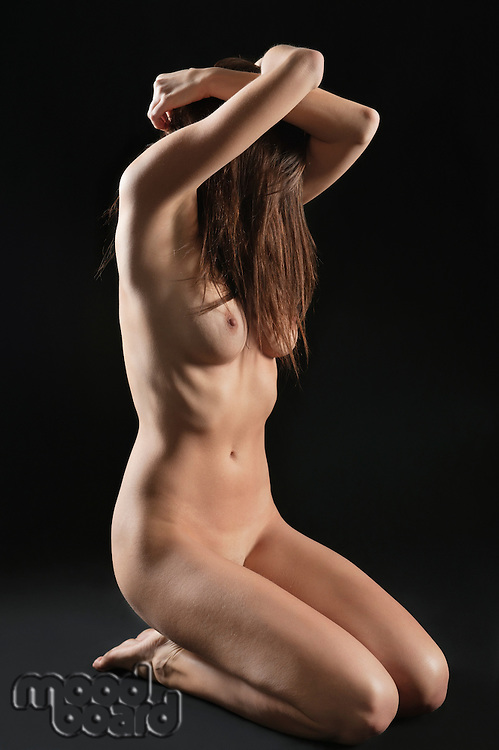 Young woman sitting nude over black background