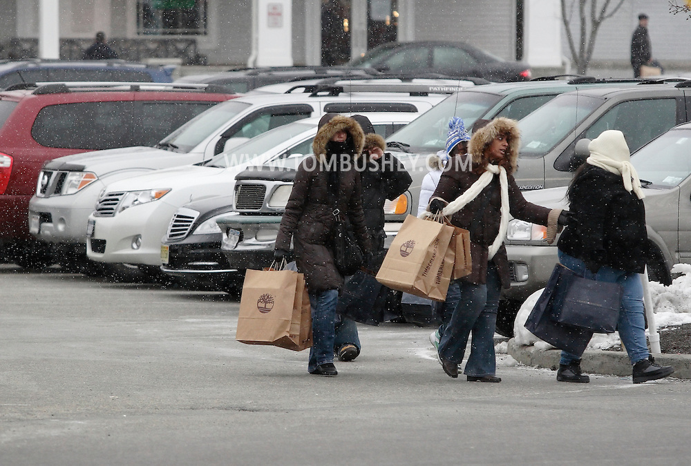Central Valley, New York - Shoppers carrying bags of merchandise walk through a parking lot at Woodbury Common Premium Outlets on Dec. 19, 2009, the Saturday before Christmas. Woodbury Common has 220 stores featuring famous designer brands.