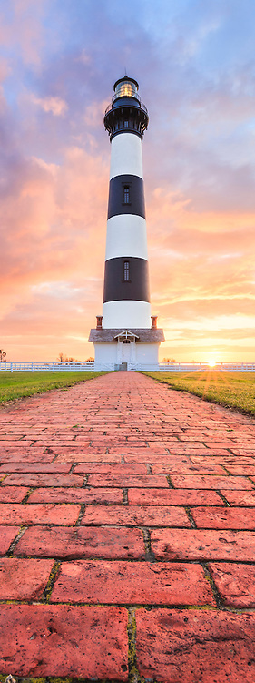 A brick path leading to Bodie Island Lighthouse at sunrise on the Outer Banks of North Carolina.