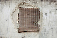 A torn bamboo curtain covers a small window in a temple of Hanoi, Vietnam, Southeast Asia