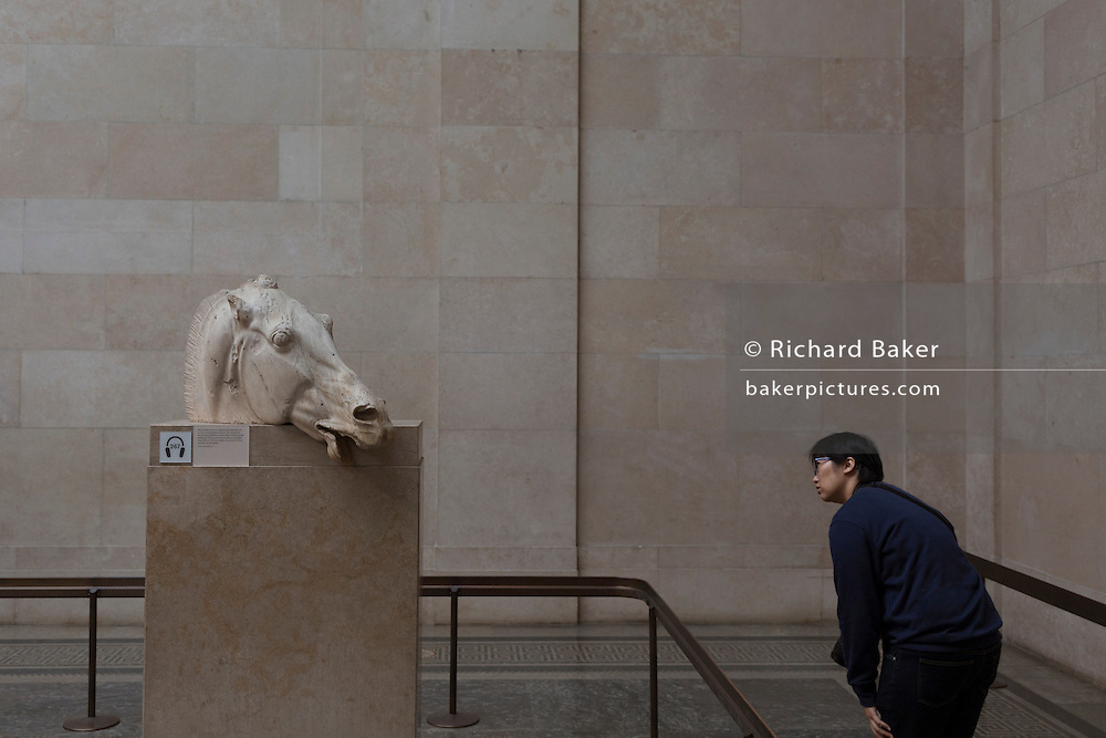 A visitor leans to learn about the The Head of the Horse of Selene, part of the British Museum's Elgin Marbles that originate from the Parthenon in Athens, on 28th February 2017, in London, England.