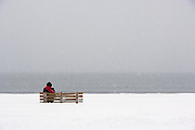 Lone figure sits on park bench on the beach in winter snowstorm