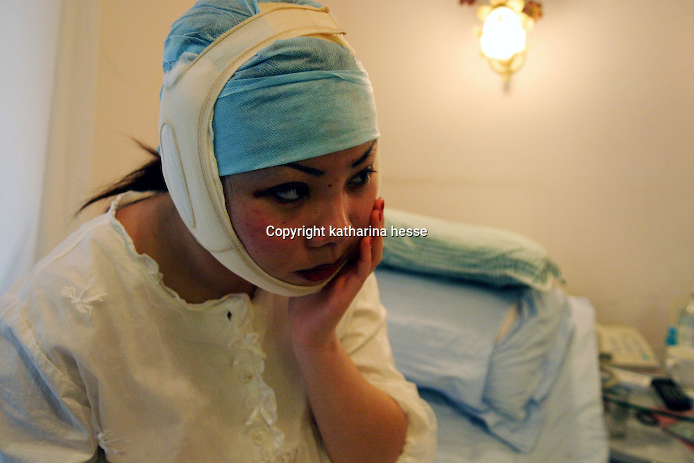 BEIJING, 24. November 2004 : Meng Ge, 24, touches her face in pain a day after her facial surgery in a hospital in Beijing, 24.November, 2004, in China. Meng had her nose  lifted, got a double eye-lit, her front widened and in addition part of her jaw bones taken off in order to make her face look smaller. Meng says the experience is very painful and if she had known in advance, she'd not have done it...Beauty business is booming in China. Sales in beauty related businesses and products are worth more than 7 billion USD last year.      ..Whereas in Mao Zedong's China, even pigtails were seen as a sign of vanity (and had to be cut off) , nowadays, urban Chinese women seek about every means in order to distinguish themselves from the masses.  This year Beijing will organize the worl'd first beauty pageant for women had had plastic surgery in early December...